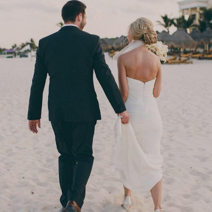Our bride Lisa walking the beach with her new husband. Dress: Nicole Miller
