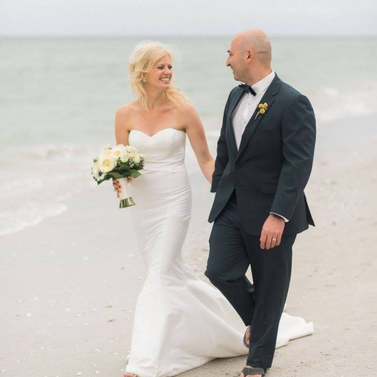 Our bride Molly walking along the beach hand-in-hand as a Mrs.! Dress: Nicole Miller 'Dakota'